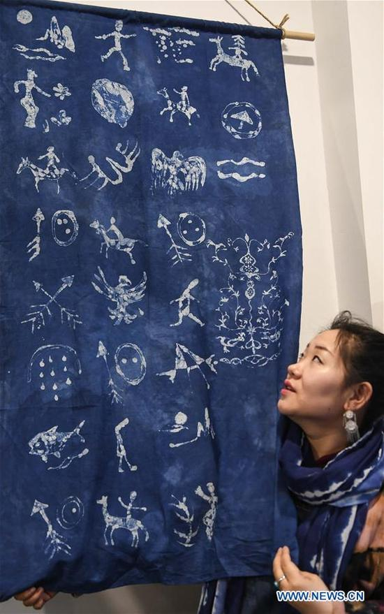 Li Andi shows shaman-themed marks on cloth in Changchun, northeast China's Jilin Province, April 11, 2018. Li studied folk arts and crafts design and graduated from Jilin Agricultural University in 2006. Since 2015, she has started to research shaman culture and designed related products at her studio. She opened a maker shop in Changchun in March 2018 and wants to protect the traditional shaman culture through her product design. (Xinhua/Wang Haofei)