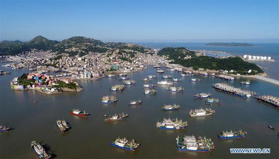 Aerial photo taken on July 9, 2018 shows fishing boats at berth at Ruoshan harbor in Wenling City, east China's Zhejiang Province. A yellow-level alert has been issued and third-level emergency response has been activated to cope with approaching typhoon Maria, the eighth typhoon this year, in China's coastal provinces. (Xinhua/Zhou Xuejun)