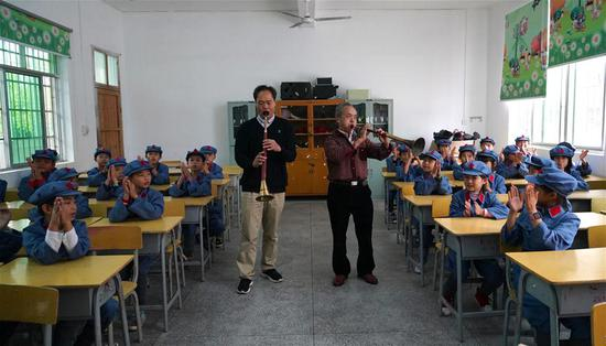 Xiao Qinghua (R, center) and his apprentice Guan Shoulin play the suona horn for students at the Changzhengyuan primary school in Yudu County, east China's Jiangxi Province, on Oct. 11, 2018. Xiao, an inheritor of the national intangible cultural heritage