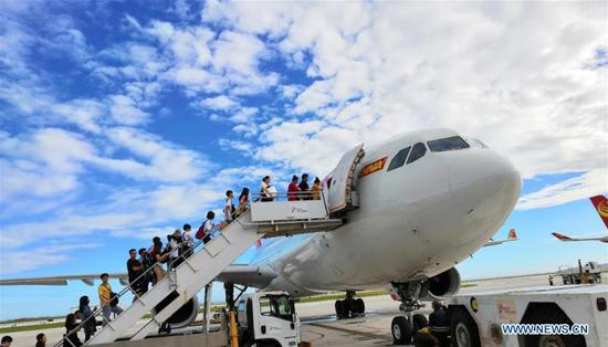 Chinese tourists get on board to fly back home in Saipan, the Commonwealth of the Northern Mariana Islands (CNMI), Oct. 28, 2018. Some 1,500 Chinese tourists trapped in Saipan by Super Typhoon Yutu started to fly back home on Sunday. (Xinhua)
