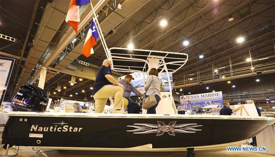 A boat salesman talks with visitors at Houston International Boat, Sport & Travel Show in Houston, the United States, on Jan. 8, 2019. Over 1,000 boats are on display during the annual show from Jan. 4 to Jan. 13. Many retail venders use the
