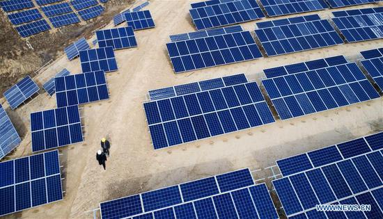 In this aerial photo taken on Nov. 7, 2018, workers patrol a photovoltaic power station built under an inter-village poverty relief program in Huojiaping Village of Yihe Township, Suide County, northwest China's Shaanxi Province, Nov. 7, 2018. Located on the Loess Plateau, Suide County has abundant sunshine and idle lands which are ideal for the construction of photovoltaic power stations. Currently, local authorities are working with a provincial branch of electricity service provider State Grid on a 33-megawatt photovoltaic power station. (Xinhua/Liu Xiao)