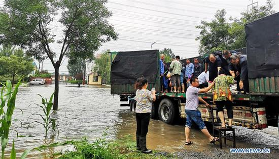 Photo taken with a mobile phone shows villagers getting on a truck to move to a relocation site in Fangjiaqiao Village of Zouping, east China's Shandong Province, Aug. 12, 2019. More than 30,000 local residents in Zouping have been relocated as the water level of Xiaofu River rises due to rainfall caused by Typhoon Lekima. (Xinhua/Fan Changguo)