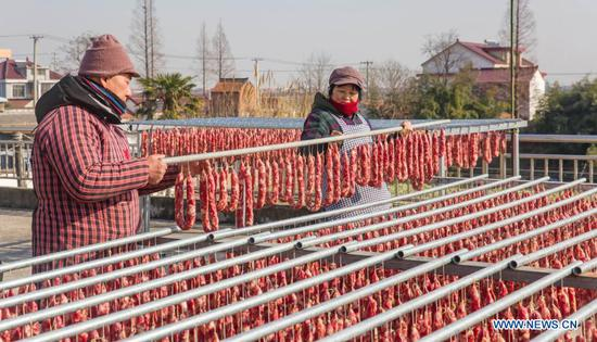 Villagers air-dry Lunar New Year sausages in Dagong Township, Hai'an City, Nantong, east China's Jiangsu Province, Jan. 10, 2021. Lunar New Year ranks among the most important festivals in China, and the celebrations are multifaceted, including food. When the Lunar New Year comes, people across China make a variety of snacks which they believe will bring good fortune. (Photo by Xiang Zhonglin/Xinhua)