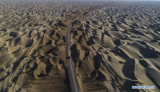 Aerial photo taken on July 5, 2018 shows the desert road under construction in Taklimakan desert in northwest China's Xinjiang Uygur Autonomous Region. An over 300-km-long desert road, linking Xinjiang's Yuli County to remote Qiemo County, is now under construction. It's the third that-kind-of road crossing China's largest desert Taklimakan nicknamed