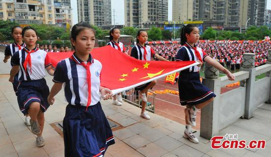 Pupils hold flag-raising ceremony at Yushui No. 6 primary school in Jiangxi Province, Sept. 1, 2019. New semester began in China. (Photo/China News Service)