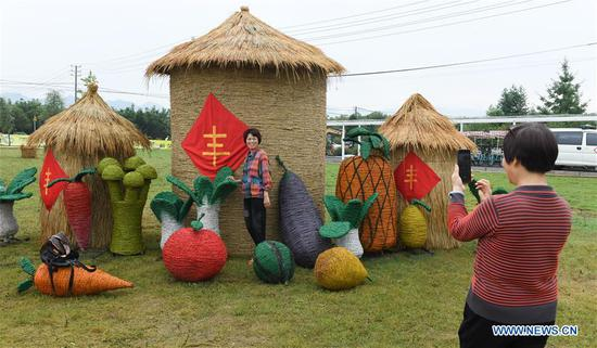 A visitor poses for a photo with figures made with straw during an event celebrating the Chinese Farmers' Harvest Festival in Datong Town of Jiande City, east China's Zhejiang Province, Sept. 22, 2020. (Xinhua/Weng Xinyang)