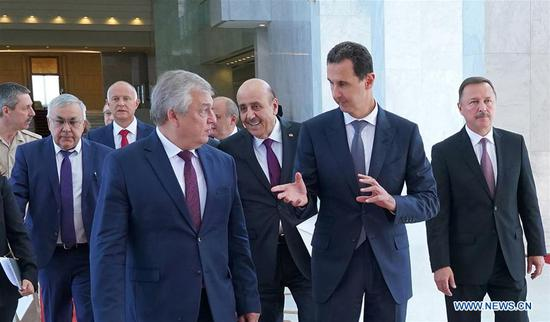 Syrian President Bashar al-Assad (R, Front) speaks with Russian president's Special Envoy to Syria Alexander Lavrentiev (L, Front) in Damascus, Syria, on Sept. 15, 2019. Bashar al-Assad on Sunday received Alexander Lavrentiev and discussed with him the tripartite summit that will take place Monday in Ankara, according to the Syrian presidential media office. (Syrian Presidency/Handout via Xinhua)