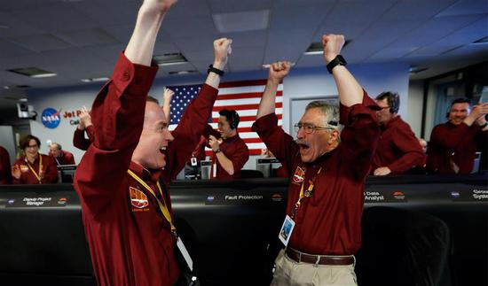 NASA engineers Kris Bruvold (left) and Sandy Krasner (right) react after the successful landing by the InSight spacecraft on the planet Mars from the Mission Support area in the Space Flight Operations facility at the NASA Jet Propulsion Laboratory in Pasadena, California on November 26, 2018.