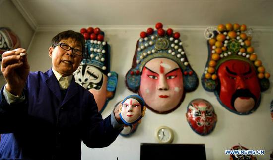 Zhang Zhi introduces the making process of facial makeup artworks at his home in Shijiazhuang, north China's Hebei Province, April 12, 2019. Zhang Zhi, an 82 year-old retiree, has made over 1,000 facial makeup artworks after his retirement in the past 25 years. He is dedicated to promote the art. (Xinhua/Chen Qibao)