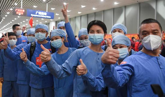 Medics supporting virus-hit Hubei Province gesture to greeters upon their arrival at Guangzhou South Railway Station in Guangzhou, south China's Guangdong Province, March 20, 2020. Medical assistance teams from Guangzhou, which consists of over 1,000 members, left Hubei Province in batches as the epidemic outbreak in the hard-hit province has been subdued. (Xinhua/Deng Hua)