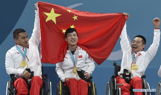Gold medalists China's Wang Haitao, Chen Jianxin, Liu Wei (L to R) celebrate on the podium during the awarding ceremony for wheelchair curling at the 2018 PyeongChang Winter Paralympic Games at Gangneung, South Korea, March 17, 2018. China beat Norway in the final 6-5 to claim the title of the event, which is also China's first-ever Winter Paralympic medal with gold. (Xinhua/Xia Yifang)