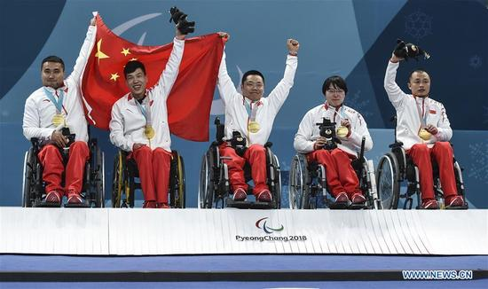 Gold medalists China's Wang Haitao, Chen Jianxin, Liu Wei, Wang Meng and Zhang Qiang (L to R) celebrate on the podium during the awarding ceremony for wheelchair curling at the 2018 PyeongChang Winter Paralympic Games at Gangneung, South Korea, March 17, 2018. China beat Norway in the final 6-5 to claim the title of the event, which is also China's first-ever Winter Paralympic medal with gold. (Xinhua/Xia Yifang)