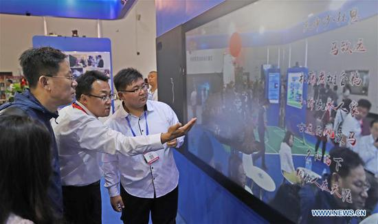 Visitors view a systematic demonstration of a smart blackboard during the 16th China International Software & Information Service Fair in Dalian, northeast China's Liaoning Province, June 12, 2018. The service fair, with the participation of 750 exhibitors, kicked off here Tuesday. (Xinhua/Yang Qing)