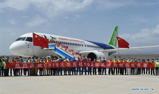 People pose for a photo in front of a C919 large passenger aircraft at the Turpan Jiaohe Airport in Turpan, northwest China's Xinjiang Uygur Autonomous Region, June 28, 2020. China's indigenously-developed C919 large passenger aircraft has started high-temperature test flights in Turpan, a city known as the land of fire in northwest China's Xinjiang Uygur Autonomous Region. The C919 conducted a successful maiden flight in 2017. Now the aircraft has started intensive test flights from various airports to make sure performance can meet airworthiness standards. (Photo by Liu Jian/Xinhua)