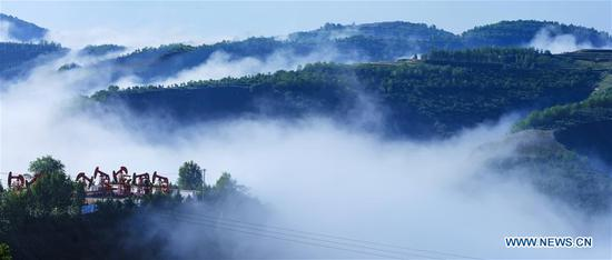 Photo taken on June 8, 2019 shows the flowing clouds over Shengli Mountain of Wuqi County in Yan'an City, northwest China's Shaanxi Province. Wuqi County has carried out a development policy since 1998 that returned farmland to forest for ecological protection and sustainable development purposes. (Xinhua/Zong Mingyuan)