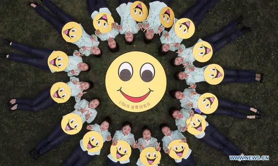 Tour guides pose with smile signs to celebrate the World Smile Day at the Slender West Lake scenic area in Yangzhou City, east China's Jiangsu Province, May 8, 2018. The World Smile Day is celebrated on May 8 every year. (Xinhua/Meng Delong)