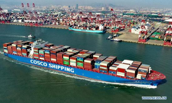 Aerial photo taken on Feb. 19, 2021 shows a cargo ship pulling out at the Qianwan Container Terminal in Qingdao, east China's Shandong Province. During this year's Spring Festival holiday, the Qingdao port has handled 12.47 million tonnes of cargo, up 12.8 percent year on year. (Photo by Zhang Jingang/Xinhua)