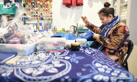 Li Andi makes tie-dyeing product at her shop in Changchun, northeast China's Jilin Province, April 11, 2018. Li studied folk arts and crafts design and graduated from Jilin Agricultural University. She has started to research shaman culture and designed related products at her studio since 2015. She opened a maker shop in Changchun in March 2018 and wants to protect the traditional shaman culture through her product design. (Xinhua/Wang Haofei)