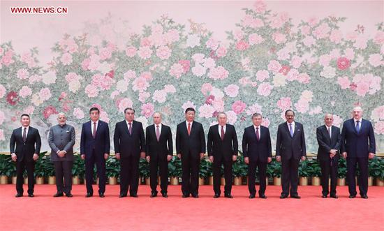 Chinese President Xi Jinping (C) and other leaders attending the 18th Shanghai Cooperation Organization (SCO) summit pose for a group photo ahead of a banquet in Qingdao, east China's Shandong Province, June 9, 2018. (Xinhua/Ding Lin)