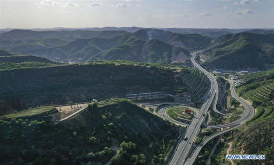 Aerial photo taken on June 5, 2019 shows hills covered with green at Wuqi County in Yan'an City, northwest China's Shaanxi Province. Wuqi County has carried out a development policy since 1998 that returned farmland to forest for ecological protection and sustainable development purposes. (Xinhua/Tao Ming)