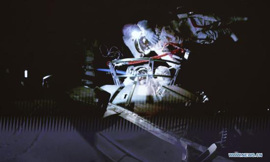 Screen image taken at Beijing Aerospace Control Center on July 4, 2021 shows Chinese astronauts conducting extravehicular activities (EVAs) out of the space station core module Tianhe. Chinese astronauts Liu Boming and Tang Hongbo had both slipped out of the space station core module Tianhe by 11:02 a.m. (Beijing Time) on Sunday, starting EVAs, according to the China Manned Space Agency (CMSA). Donning new-generation homemade EMU (extravehicular mobility unit) spacesuits Feitian, meaning flying to space, the two astronauts have completed installing the foot restraints and extravehicular working platform on the mechanical arm, the CMSA said. They will continue to work together to install other relevant extravehicular equipment with the aid of the mechanical arm, it said. Astronaut Nie Haisheng has been staying inside Tianhe in cooperation with Liu and Tang for their EVAs. (Xinhua/Jin Liwang)