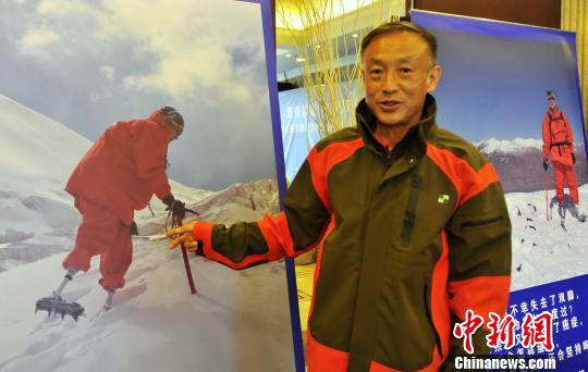 Xia Boyu, 69, points to his photo in which he climbs on the summit of Mount Qomolangma. (Photo/China News Service)