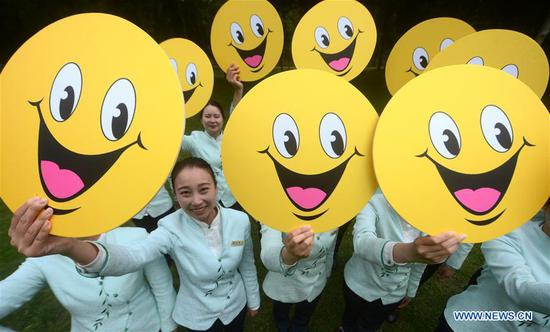 Tour guides show smile signs to celebrate the World Smile Day at the Slender West Lake scenic area in Yangzhou City, east China's Jiangsu Province, May 8, 2018. The World Smile Day is celebrated on May 8 every year. (Xinhua/Meng Delong)