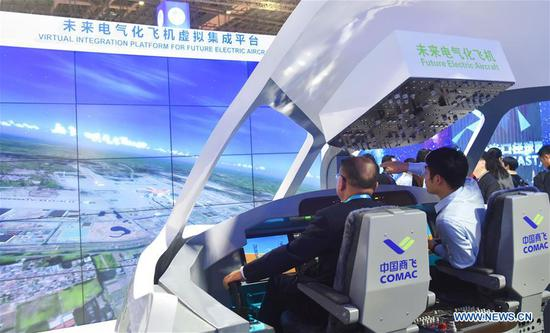 Visitors sit in a model cockpit at the China pavilion during the second China International Import Expo (CIIE) in Shanghai, east China, Nov. 8, 2019. The China pavilion showcases achievements China has made over the past 70 years, as well as its culture and landscape. (Xinhua/Wei Hai)