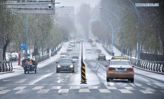 Cars drive slowly on a snowy and icy road in Changchun, capital of northeast China's Jilin Province, Nov. 13, 2019. A snowfall hit Changchun on Wednesday. (Xinhua/Yan Linyun)