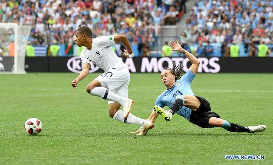 Diego Laxalt (R) of Uruguay vies with Kylian Mbappe of France during the 2018 FIFA World Cup quarter-final match between Uruguay and France in Nizhny Novgorod, Russia, July 6, 2018. (Xinhua/Chen Cheng)