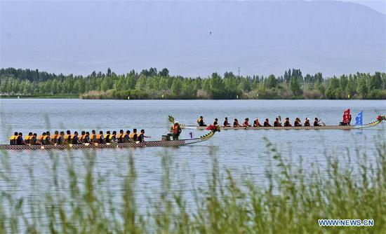 People take part in a dragon boat race to celebrate the Dragon Boat Festival at a Dahuwan Reservoir at Gaotai County in Zhangye City, northwest China's Gansu Province, on June 6, 2019. The Dragon Boat Festival falls on the fifth day of the fifth month of the Chinese lunar calendar, or June 7 this year. (Xinhua/Wang Jiang)