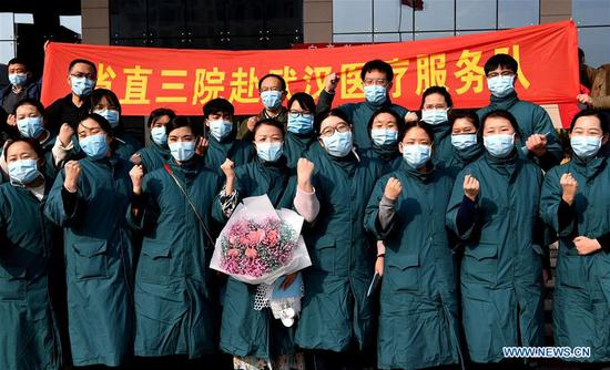 Medical workers pose for a group photo before setting off for Wuhan in Hubei Province, in Zhengzhou, central China's Henan Province, Feb. 2, 2020. The second batch of 122 medical workers from Henan set off on Sunday to aid the coronavirus control efforts in Wuhan. (Xinhua/Li An)