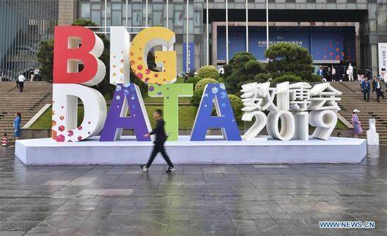 A visitor walks past a sign of China International Big Data Industry Expo 2019 in Guiyang, southwest China's Guizhou Province, May 26, 2019. The expo on big data opened Sunday in Guizhou Province, focusing on the latest innovation of the technology and its applications. The four-day expo will be attended by 448 enterprises from 59 countries and regions, according to the organizing committee. (Xinhua/Ou Dongqu)