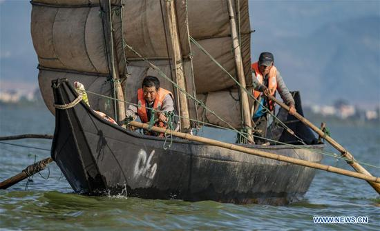 Fishermen Zhang Kaidi (L) and Li Peiguang row a fishing boat on Dianchi Lake in Kunming, southwest China's Yunnan Province, Oct. 23, 2019. Dianchi Lake officially opened for fishing on Oct. 16. To protect the ecological environment of Dianchi Lake, only whitebaits and small shrimps are allowed to be fished during the 30 day fishing season this year, and any other aquatic products harvest are prohibited. In the late 1980s, Dianchi Lake became murky because of the industrial and domestic waste discharged into it. To protect Dianchi Lake, the central government and Yunnan provincial authorities then implemented a series of measures to restore its lost splendor after decades of severe pollution. After over 30 years of endeavors, water quality of Dianchi Lake has been improved. Water quality in the Dianchi Lake remained to grade IV in the first half of 2019. (Xinhua/Jiang Wenyao)