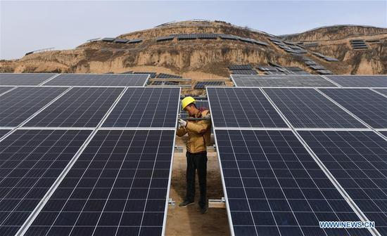 A worker checks solar panels at a photovoltaic power station built under an inter-village poverty relief program in Huojiaping Village of Yihe Township, Suide County, northwest China's Shaanxi Province, Nov. 7, 2018. Located on the Loess Plateau, Suide County has abundant sunshine and idle lands which are ideal for the construction of photovoltaic power stations. Currently, local authorities are working with a provincial branch of electricity service provider State Grid on a 33-megawatt photovoltaic power station. (Xinhua/Liu Xiao)