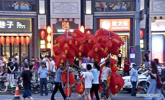 Workers carry red lanterns for decorating a night market at Beixinqiao area in Beijing, capital of China, Aug. 7, 2019. (Xinhua/Li Xin)