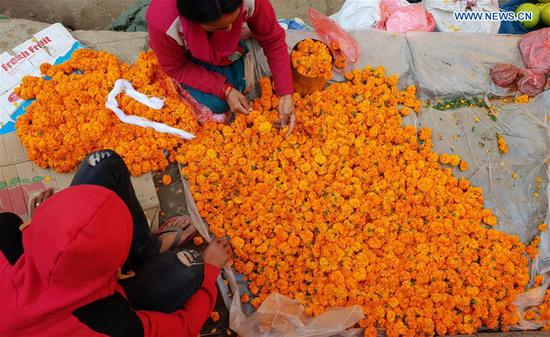 People prepare marigold garlands for Tihar festival at a local market in Kathmandu, Nepal, on Nov. 6, 2018.