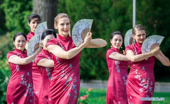 Chinese and Austrian models present cheongsam, a traditional Chinese dress also known as Qipao, during a cheongsam show in Vienna, Austria, on Aug. 27, 2019. The 2019 Hangzhou Global Qipao Festival was held in Vienna on Tuesday. (Photo by Wang Zhou/Xinhua)