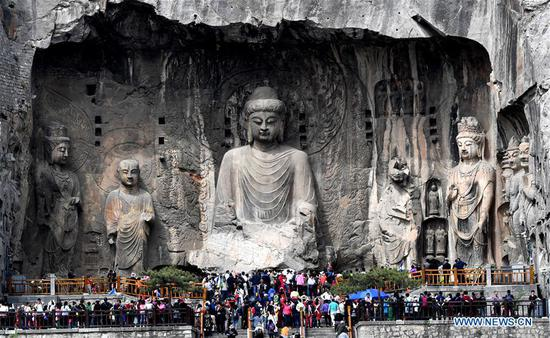 People visit the Longmen Grottoes in Luoyang, central China's Henan Province, April 11, 2018. The Longmen Grottoes has started to greet its boom season for tourism since April. (Xinhua/Zhu Xiang)