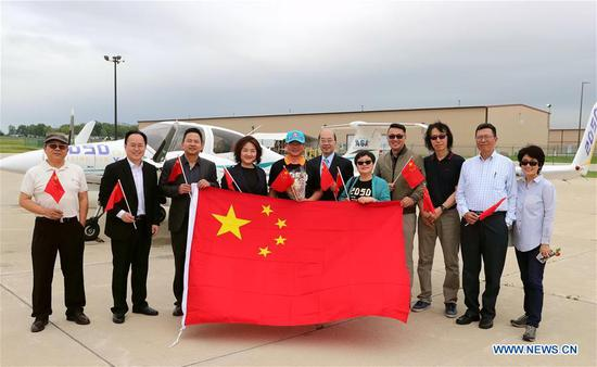 Zhang Bo (5th L) poses for photos in front of his aircraft while receiving a warm welcome from family members and friends at an airport in Chicago, the United States, on June 9, 2019. After flying 68 days and making 50 stops, 57-year-old Bo Zhang completed his second around-the-world flight and landed in Chicago on Sunday morning. On April 2, Zhang kicked off the flight in the same airport in Chicago. In 68 days, he flied through 21 countries in three continents and over three oceans, with total mileage reaching 41,000 kilometers. (Xinhua/Wang Ping)