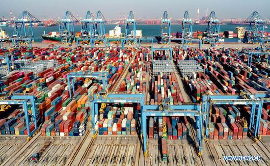Aerial photo taken on Feb. 19, 2021 shows containers being loaded on a cargo ship at the automatic dock of the Qingdao port in Qingdao, east China's Shandong Province. During this year's Spring Festival holiday, the Qingdao port has handled 12.47 million tonnes of cargo, up 12.8 percent year on year. (Photo by Zhang Jingang/Xinhua)