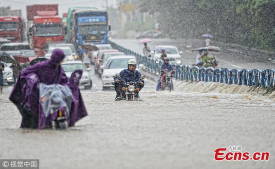 Motorcyclists drive on a flooded road after a rainstorm in Quanzhou City, East China's Fujian Province, Aug. 29, 2018. (Photo/VCG)