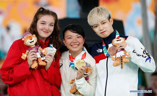 Gold medalist Japan's Ram ( C) poses with silver medalist Canada's Emma (L) and bronze medalist South Korean Yell during the awarding ceremony of the Breaking B-Girls Gold Medal Battle at the 2018 Summer Youth Olympic Games in Buenos Aires, Argentina on Oct. 8, 2018. (Xinhua/Wang Lili)