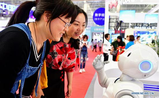 Two visitors interact with a robot at the 2nd Digital China Exhibition in Fuzhou, southeast China's Fujian Province, May 5, 2019. The 2nd Digital China Exhibition runs from May 5 to 9 at the Fuzhou Strait International Conference & Exhibition Center. (Xinhua/Wei Peiquan)