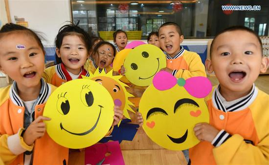 Kids demonstrate smiley cards to greet the upcoming World Smile Day at a kindergarten in Zigui County, central China's Hubei Province, May 7, 2019. World Smile Day is celebrated on May 8 every year. (Xinhua/Wang Huifu)