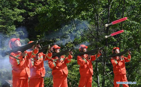 Firefighters conduct a drill at Huoditang forest farm in Ningshan County, northwest China's Shaanxi Province, May 21, 2019. (Xinhua/Liu Xiao)
