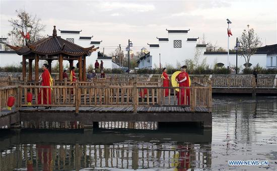 Villager models walk on the wooden trestle of a park in Houtaizi Village of Qian'an City, north China's Hebei Province, Nov. 10, 2019. The local government made great efforts to improve the rural living environment this year. After high-standard transformation and construction, a rubbish disposal pit has been turned into a beautiful park with clear water and antique buildings, becoming an attractive public place for recreation and entertainment. (Xinhua/Jin Liangkuai)