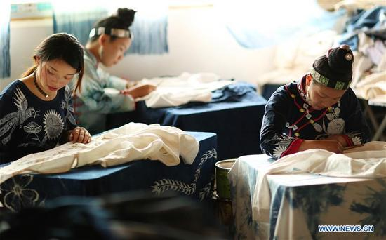 Artists make batik at a cooperative in Danzhai County, southwest China's Guizhou Province, April 9, 2018. Relying on its intangible cultural heritage, Danzhai encourages local people to develop the business such as opening experience houses for visitors. This also becomes a means of helping local people get rid of poverty with this