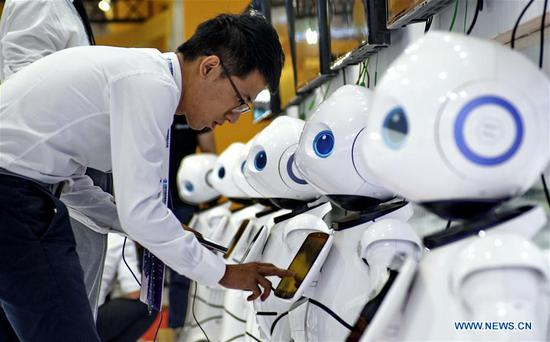A man interacts with a robot during the 2019 World Robot Conference in Daxing District of Beijing, capital of China, Aug. 20, 2019. The 2019 World Robot Conference, themed